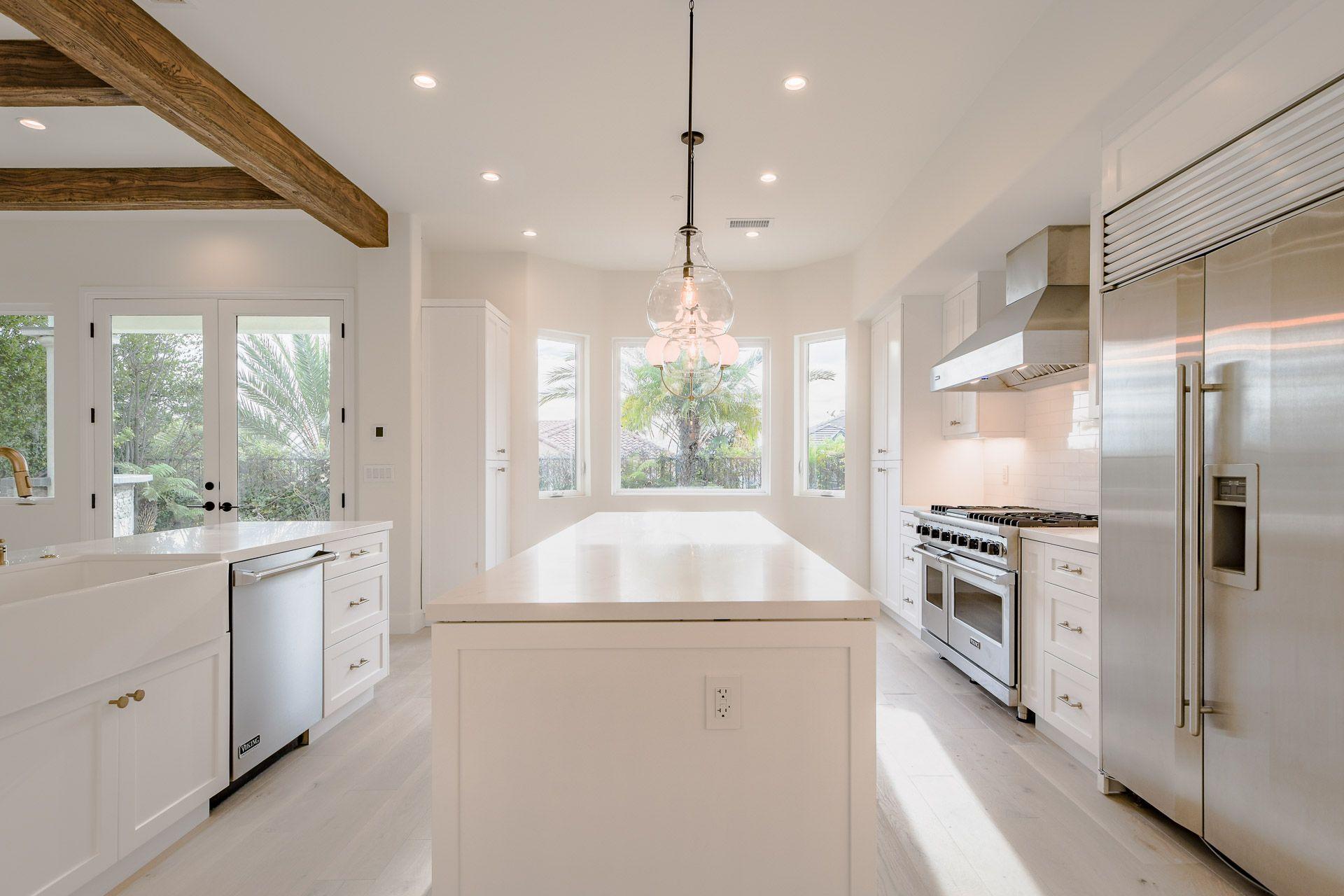 Ceiling beams, white shaker cabinets, calacatta quartz ...