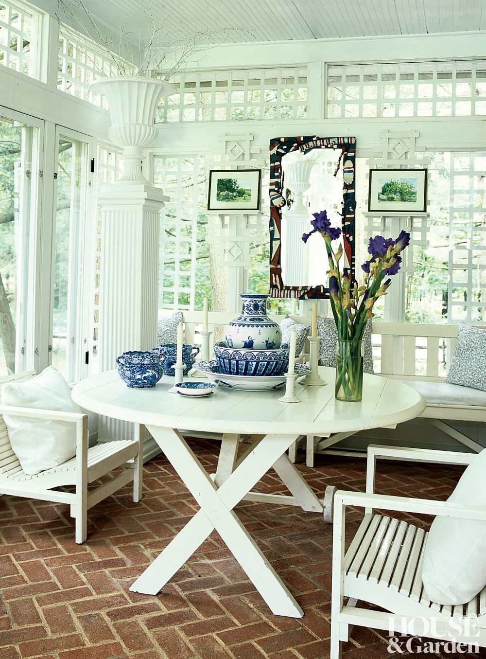 Glass and plaster trellis walls enclose a porch at designer Sheila Camera Kotur's family home in Massachusetts. Vintage garden furniture is accented with pillows.