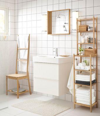 Badkamer met witte wastafelkast en stoel met handdoekenrek, spiegel ...