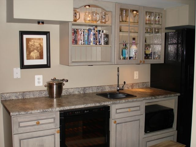 Rec Room Wet Bar Featuring Custom Cabinetry Sink Wine Cooler Refrigerator And Microwave