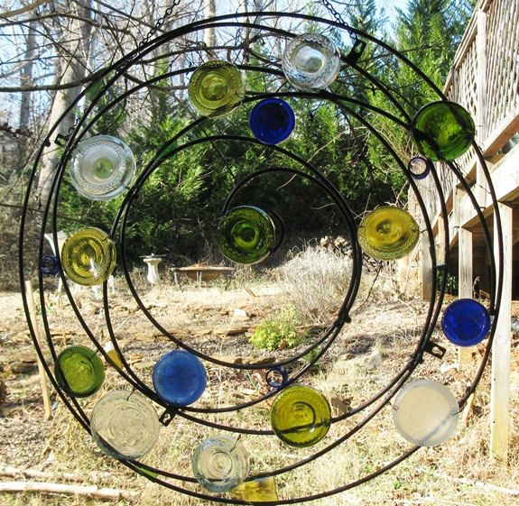 Wrought iron circle with recycled glass bottle bottoms for Recycled glass art projects