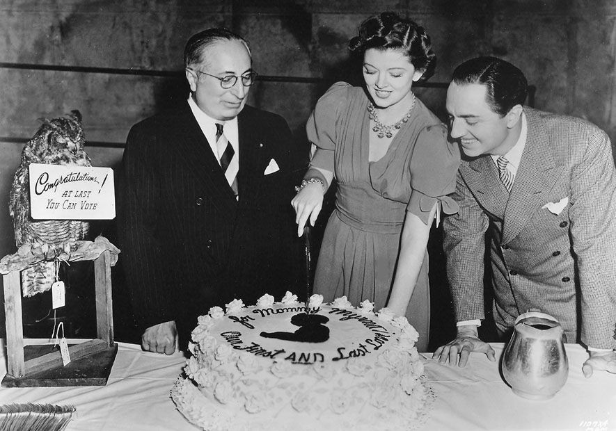 Louis B Mayer and William Powell watch as Myrna Loy cuts her