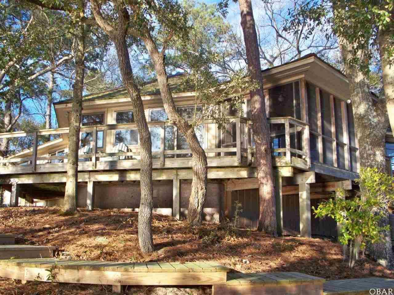 1 Point Comfort Lane Lot #17, Southern Shores, NC 27949. Once in a lifetime opportunity! Waterfront home in an X FLOOD ZONE! This highly elevated lot on Ginguite Creek affords 270 degree views and unsurpassed solitude. Lovingly landscaped with indigenous plants in a natural style, blooms will abound in season and foliage will provide canopy. Private deeded access to secluded adjoining open space will insure privacy through the years.