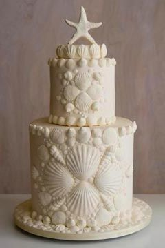 Two Tier Ivory Seashells Beach Theme Wedding Cake Decorated With Seashell Patterns An A Sta Beach Wedding Cake Beach Theme Wedding Cakes Themed Wedding Cakes