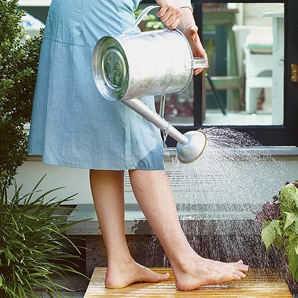 To avoid tracking in sand or soil after a day at the beach or working in the garden, set up a rinsing station just outside your door or at another convenient location. A teak bath mat provides slip-free footing and good drainage. The steady stream from an ordinary watering can cleans every unwanted speck from your feet and flip-flops or waterproof garden shoes.