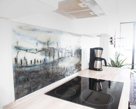 This backsplash was inspired by the view at the Storebaelt Bridge – Greyish colours with hints of blue and red.Details: JKE Kitchen. Private Home.