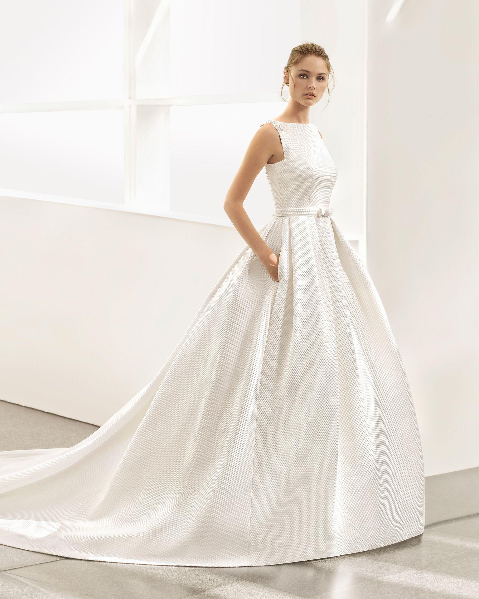 Un vestido clásico y elegante ralizado en cloqué. El cuerpo tiene una espectacular espalda joya con escote en V que se combina con una falda de volumen con blolsillos. Rosa Clará Couture 2018
