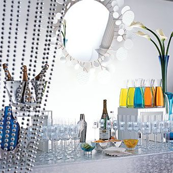 Brides: Swanky Soiree. The bar is the focal point of this celebration. Use a faux-lizard metallic cloth to drape over the table and hang a decked-out mirror over the bar. White calla lilies in blue vases add a touch of color. Cocktail glasses and decanters of Technicolor juices act as design elements, while curtains of silver beads frame the scene.