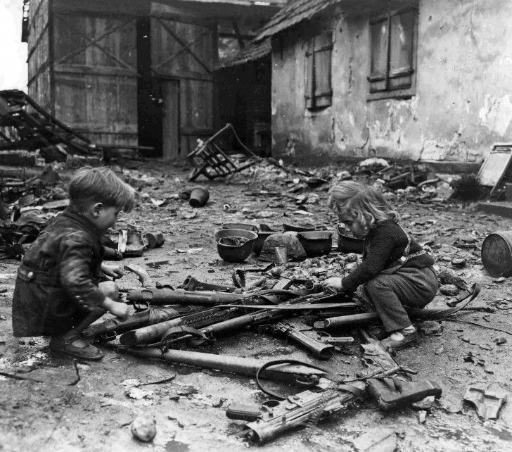 German children playing with abandoned weapons  on the street of the village Südpfalz.