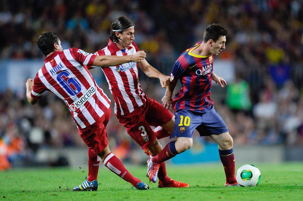 Lionel Messi of FC Barcelona duels for the ball with Koke Resurreccion (L) and Filipe Luis of Atletico de Madrid during the Spanish Super Cup second leg match between FC Barcelona and Atletico de Madrid at Nou Camp on August 28, 2013 in Barcelona, Catalonia.