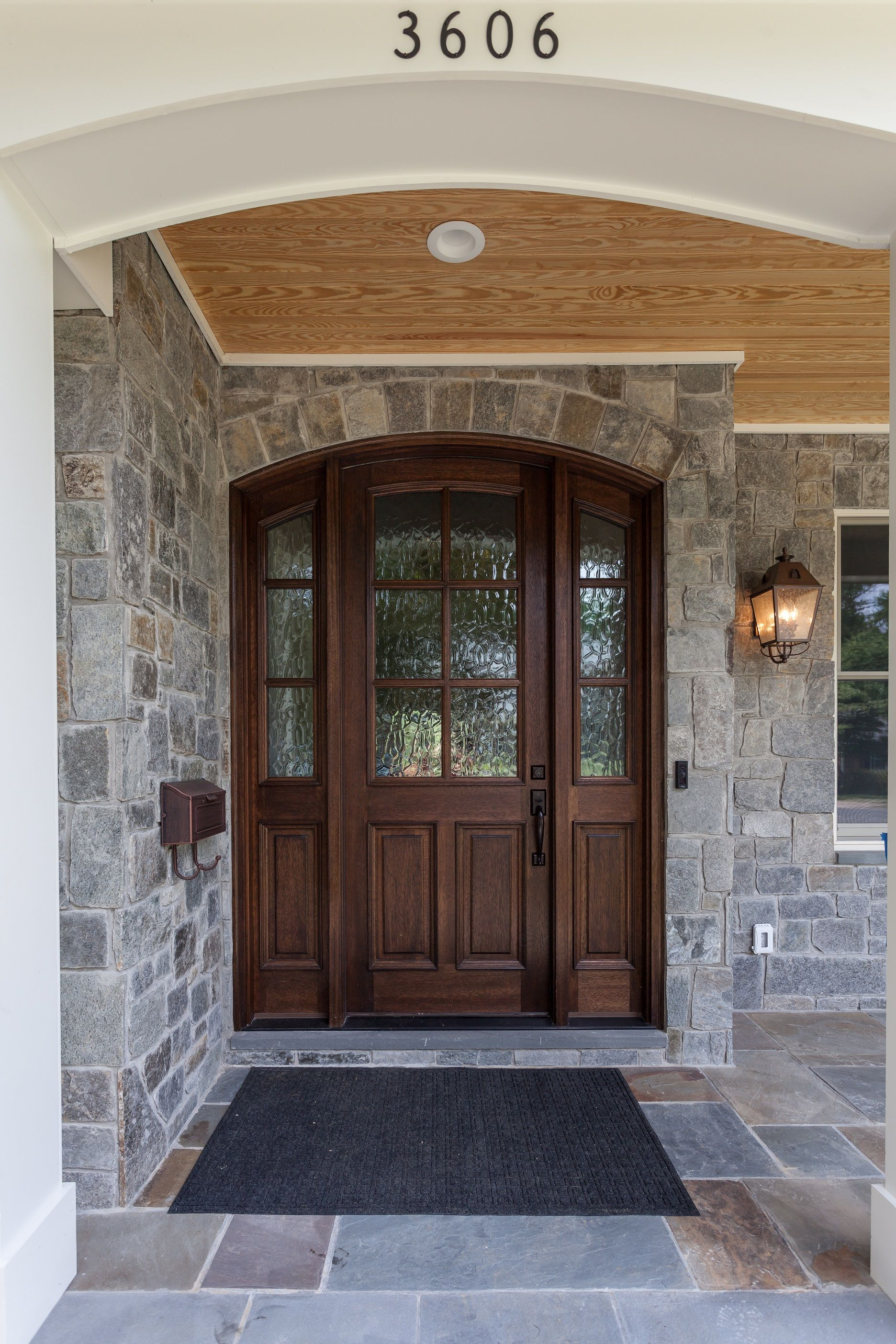 Tudor Farmhouse Inspired Exterior With Stained Arched Front Door Stone Facade And Natural Cedar Garage Door Styles Arched Exterior Doors Front Door Entryway