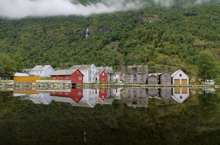 Laerdalsoyri, Norway, - Old wooden houses of Laerdalsoyri brightly reflected in still water with forest and waterfall Stock ...