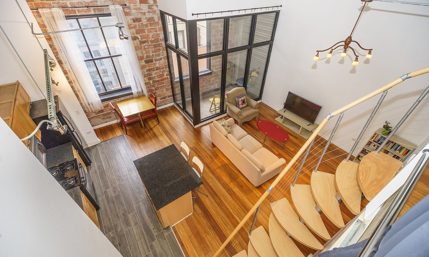 Modern loft apartment with exposed brick, pendant chandelier ...