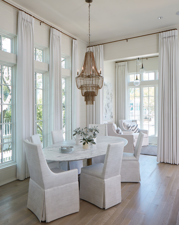 Six Offwhite Slipper Chairs Surround An Oval Marble Top Dining Magnificent Off White Dining Room Furniture Inspiration Design