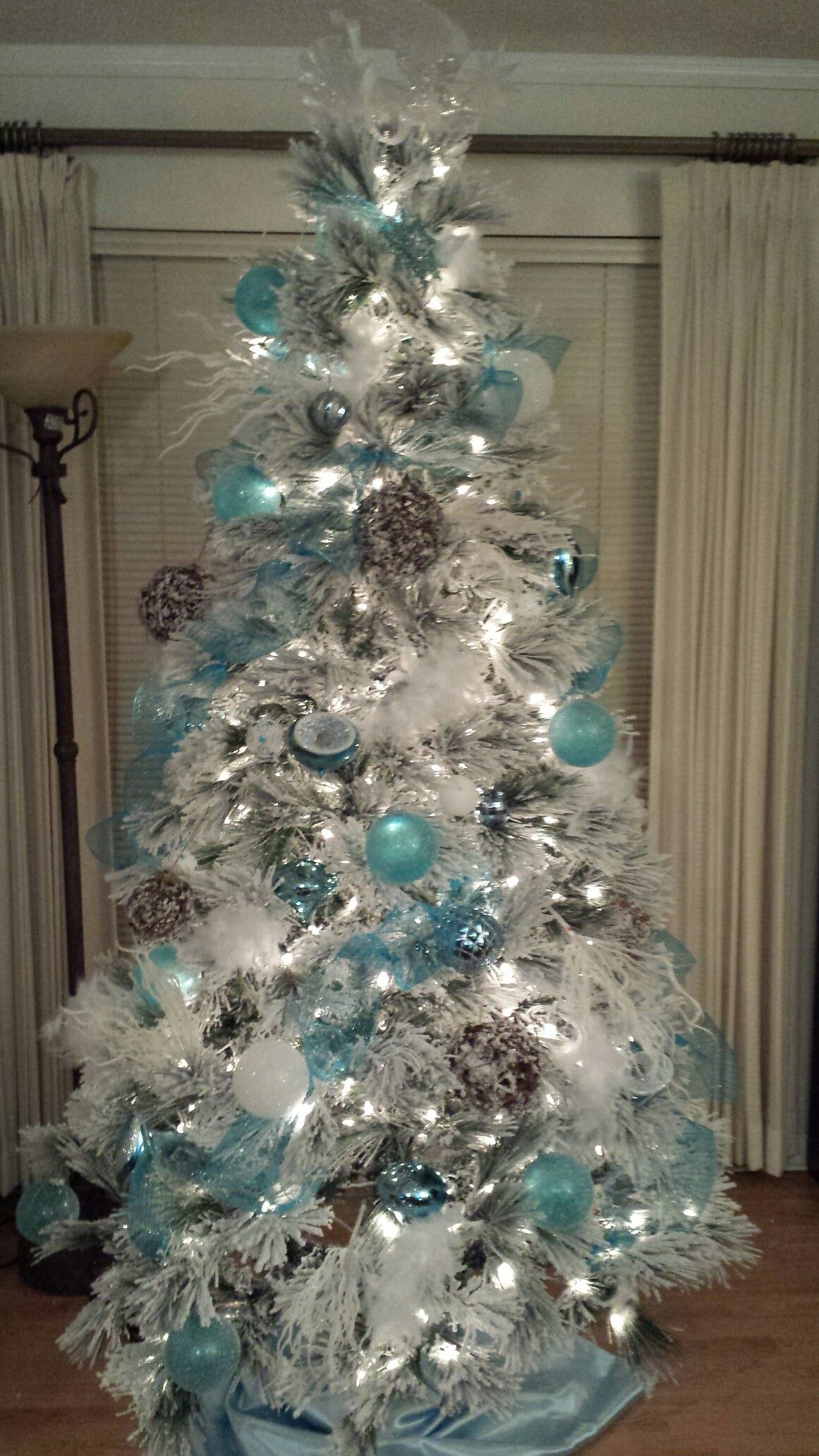 Snow White Flocked Christmas Tree Decorated With Aqua Blue Silver And Snow Vi Blue Christmas Tree White Christmas Tree Decorations White Flocked Christmas Tree