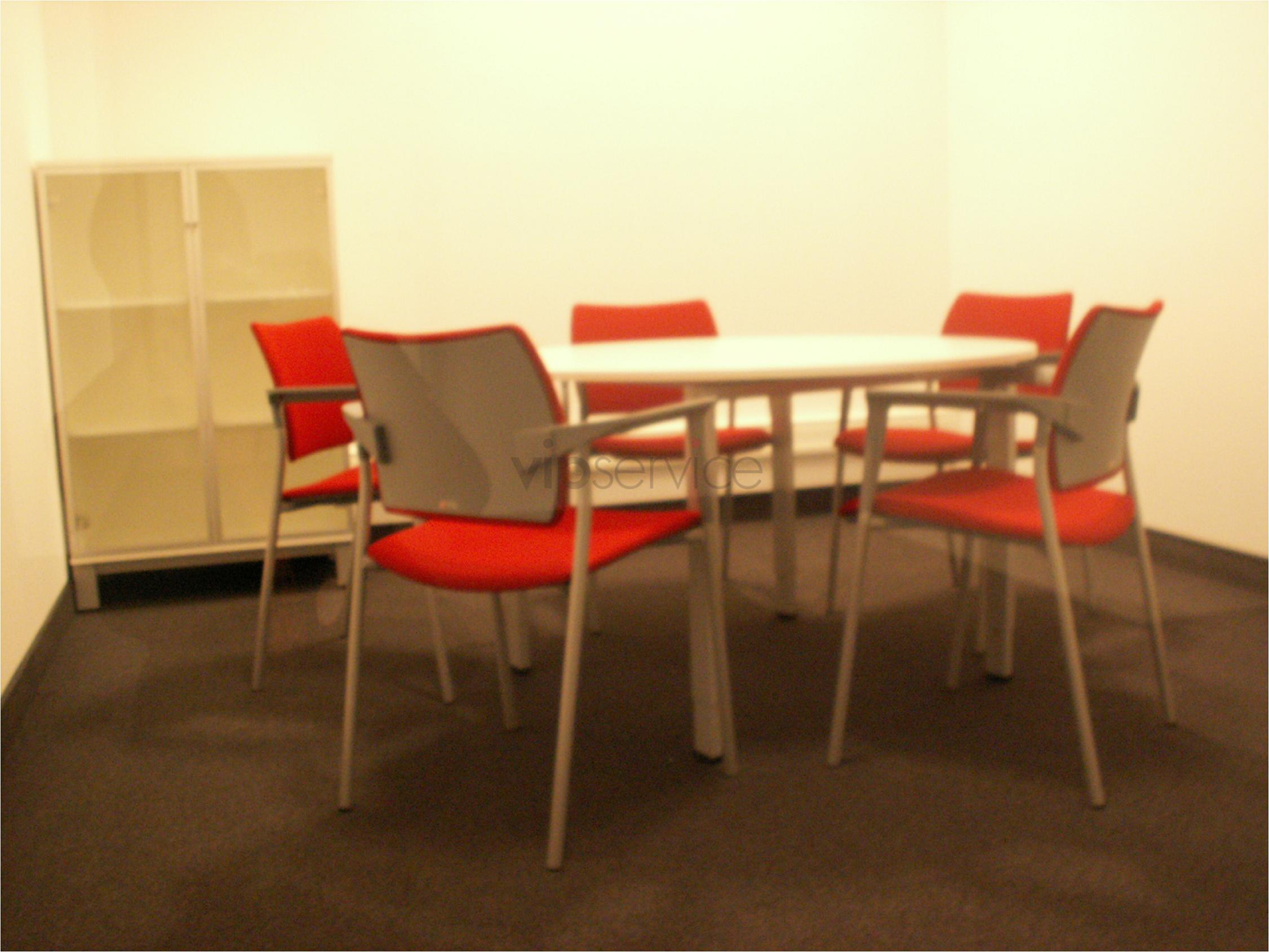 Okrągły stolik i oryginalne krzesła z czerwonymi obiciami w salce konferencyjnej.