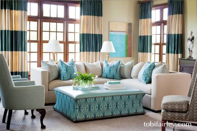 Bold patterns in this living room design by Tobi Fairley: versatile ottoman, sectional for lots of seating, giant stripes in drapery fabric