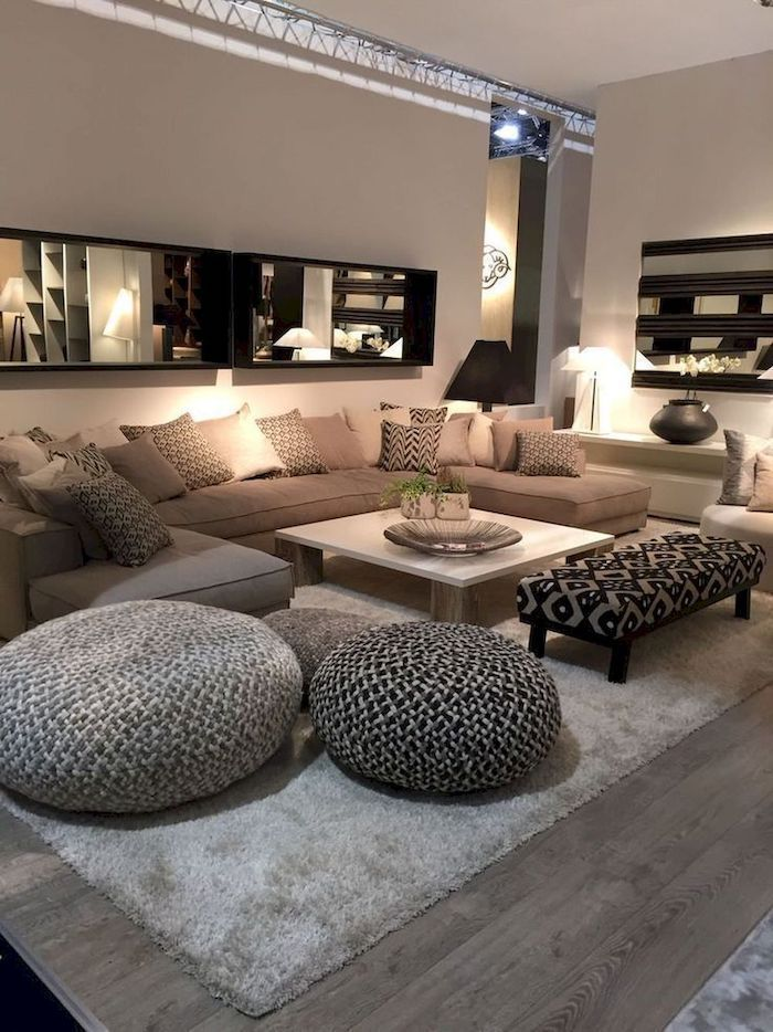 beige walls, large beige sofa with shades of beige throw pillows, wooden floor with