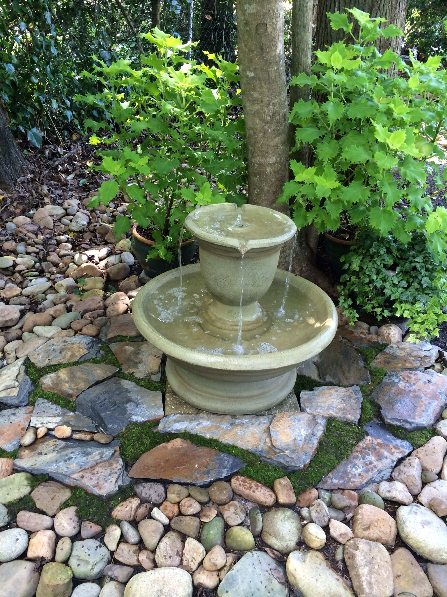 New fountain installation in the shade garden with stone and moss
