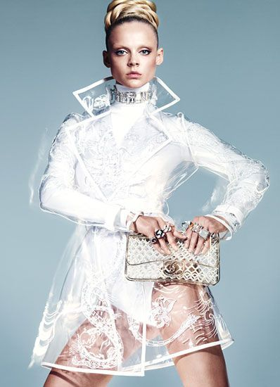 High fashion clear plastic coat with white pattern and white trim worn over  white bodysuit. 6d76ec5cc475