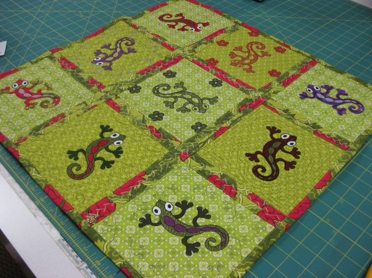 Gecko Quilt by Nancy Wilkins #quilting    This is a table topper made with embroidery motifs. It is quilted a different way - each square is backed by a larger backing that is brought to the front and used for making the sashing between the squares