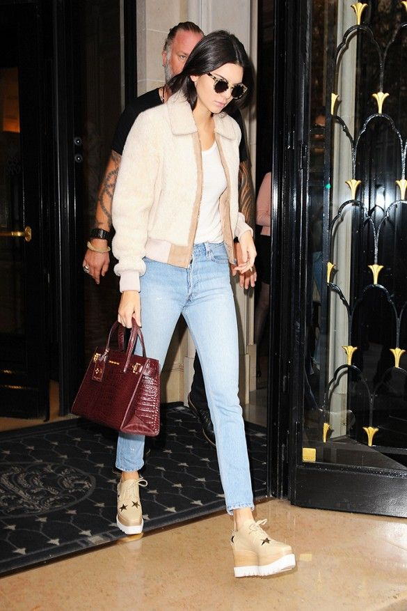 Kendall Jenner wears a white t-shirt, shearling bomber jacket, cropped jeans, Stella McCartney platform oxfords, round sunglasses, and a croc embossed burgundy tote