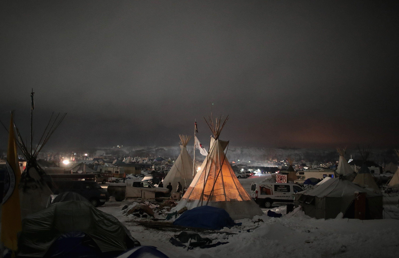 Cannon Ball, North Dakota, EUA  A noite cai sobre o campo Oceti Sakowin na borda da reserva Standing Rock Sioux. Uma vez que as manifestações contra o US $ 3,7 bilhões oleoduto Dakota Acesso começou em abril, a aplicação da lei fizeram mais de 500 prisões, com os procuradores do estado formular acusações graves, incluindo distúrbios e conspiração , contra muitos dos manifestantes