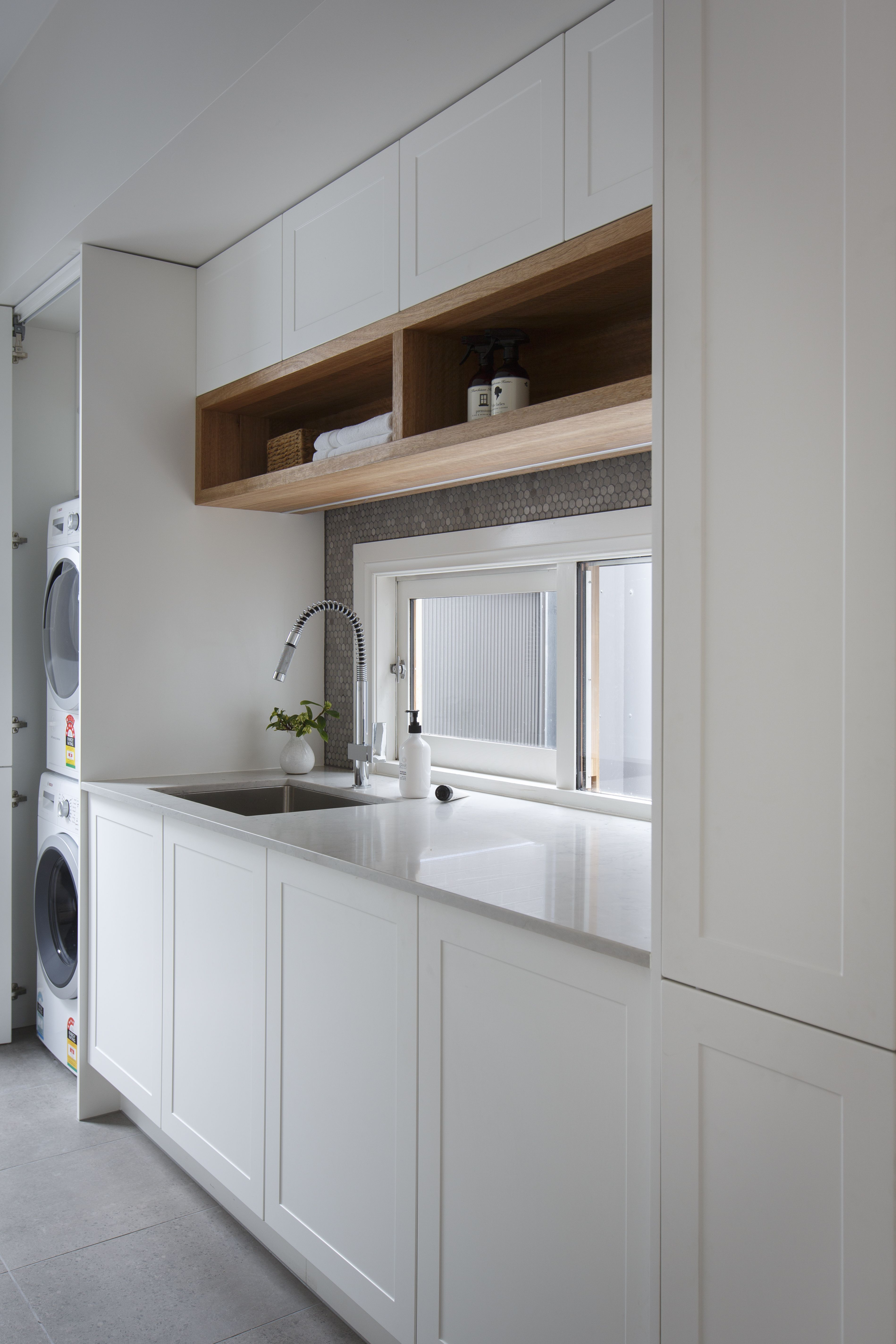 Luxe Laundry Featuring White Shaker Cabinetry And Open Timber Shelving
