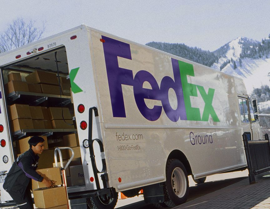 Fedex Ground Vehicle And Employee Loading Parcels For Delivery