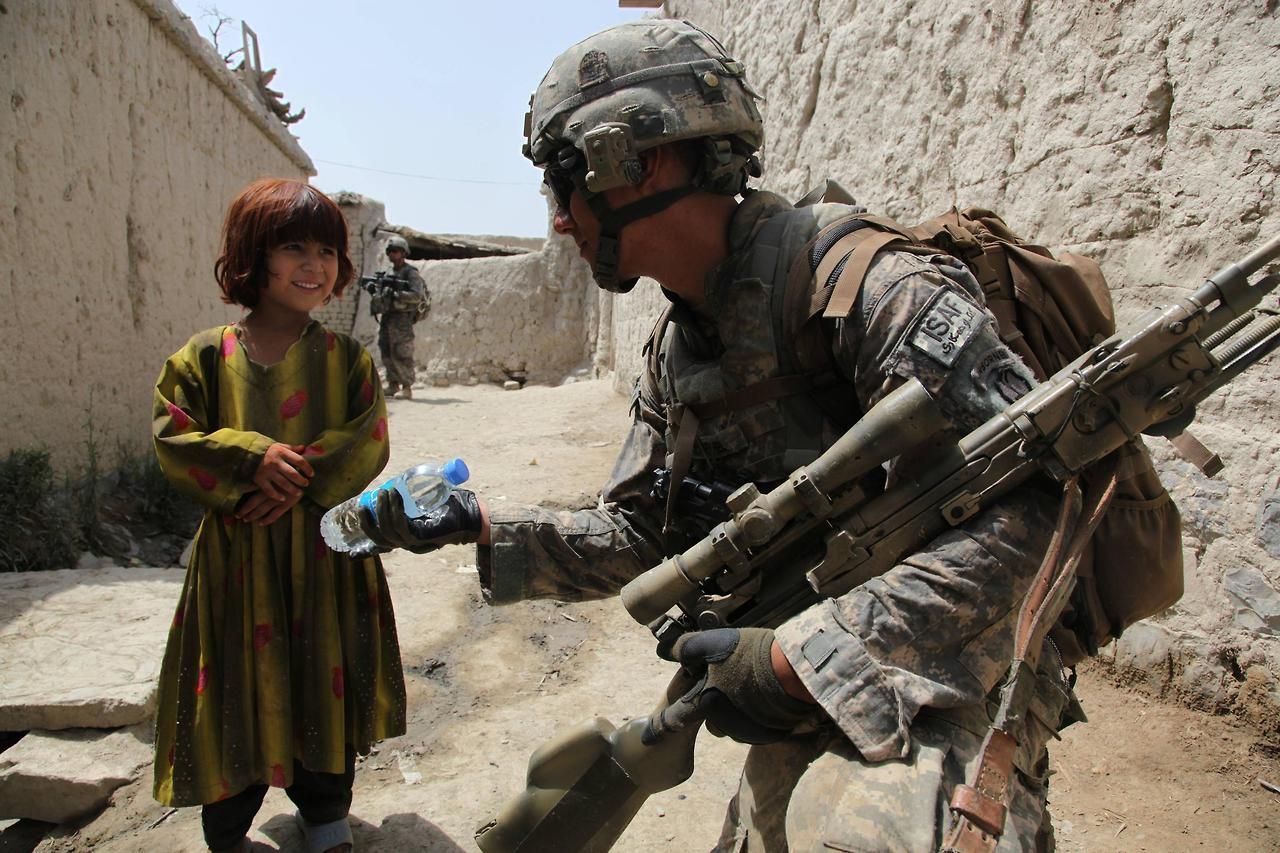 A U S Army Soldier Handing Out Water To A Young Afghan