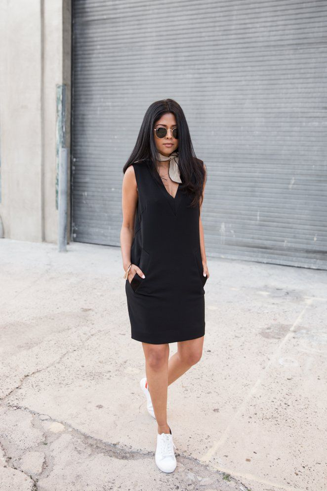 A black shift dress with a neck scarf and casual sneakers