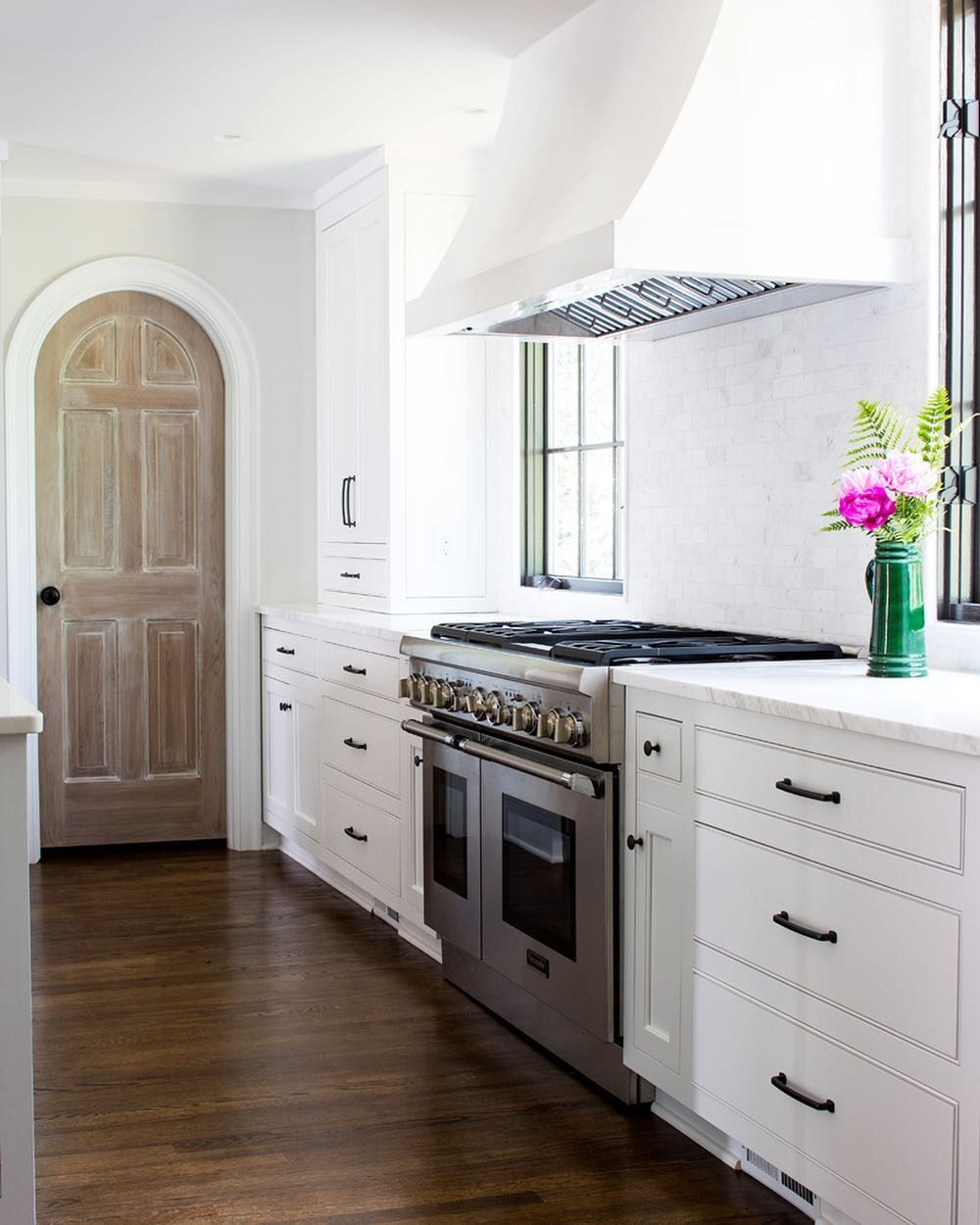 Natural wood pantry door in white kitchen remodel in