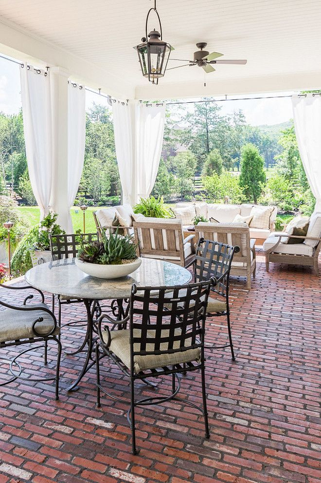 Brick floor porch with an outdoor living room and gauzy curtains ...