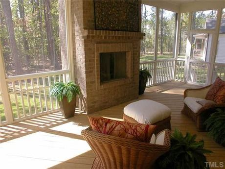 an outdoor fireplace in the center of this screened in porch creates rh pinterest ca