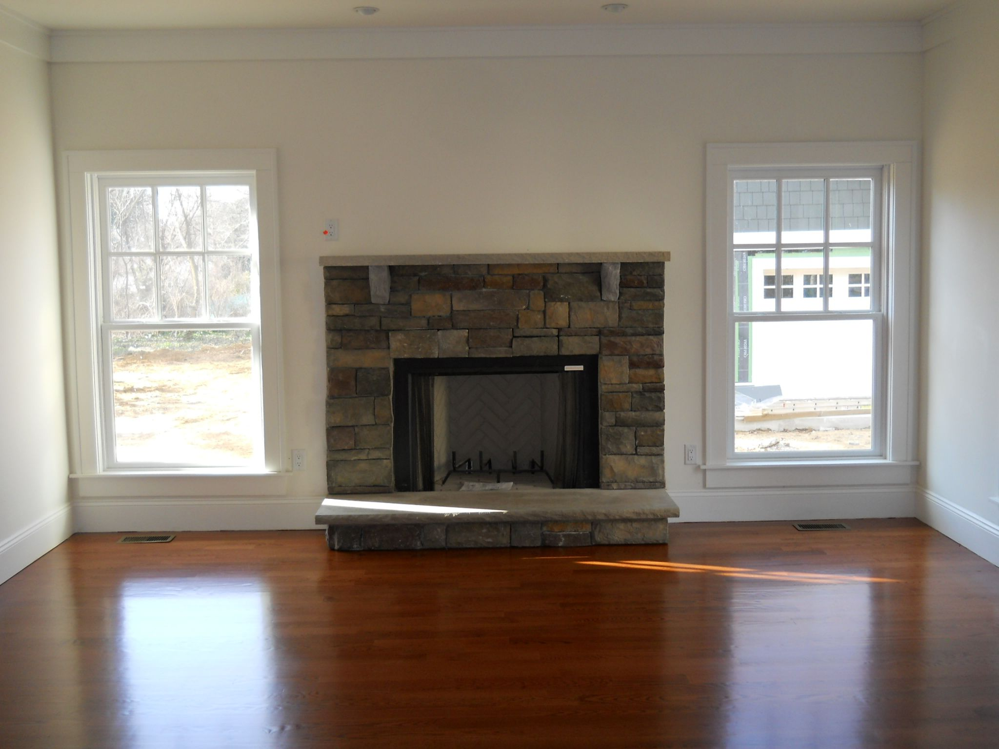 A beautiful stone fireplace is added in the home 39 s living - Fireplace between two rooms ...