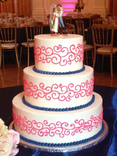 Buttercream wedding cake with hot pink scrolls and navy blue bead border