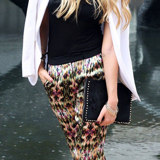 Studded leather clutch and printed trousers