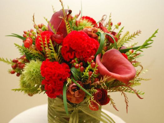 An arrangement of red cockscomb, red calla lilies, and green chestnuts