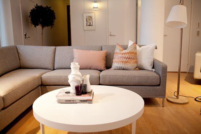 harmaa sohva, jossa ohuet jalat, valkoiset huonekalut ja värillisiä tyynyjä
