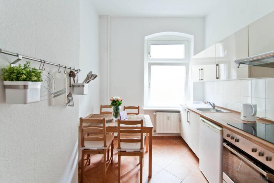 Küche mit braunem Fliesenboden, weißen Wänden, schöner ...
