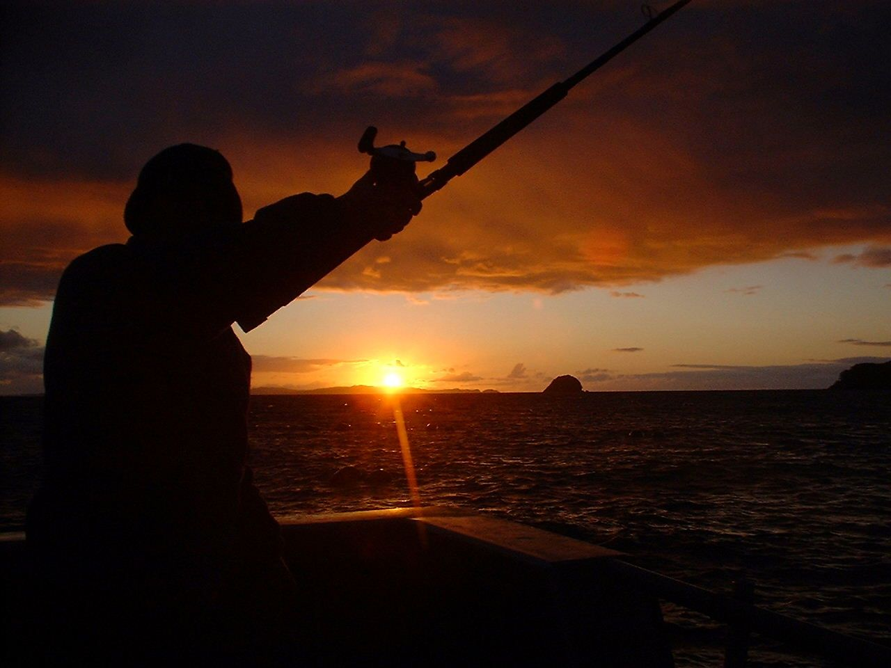 Fishing in New Zealand, silhouette on beautiful sunset