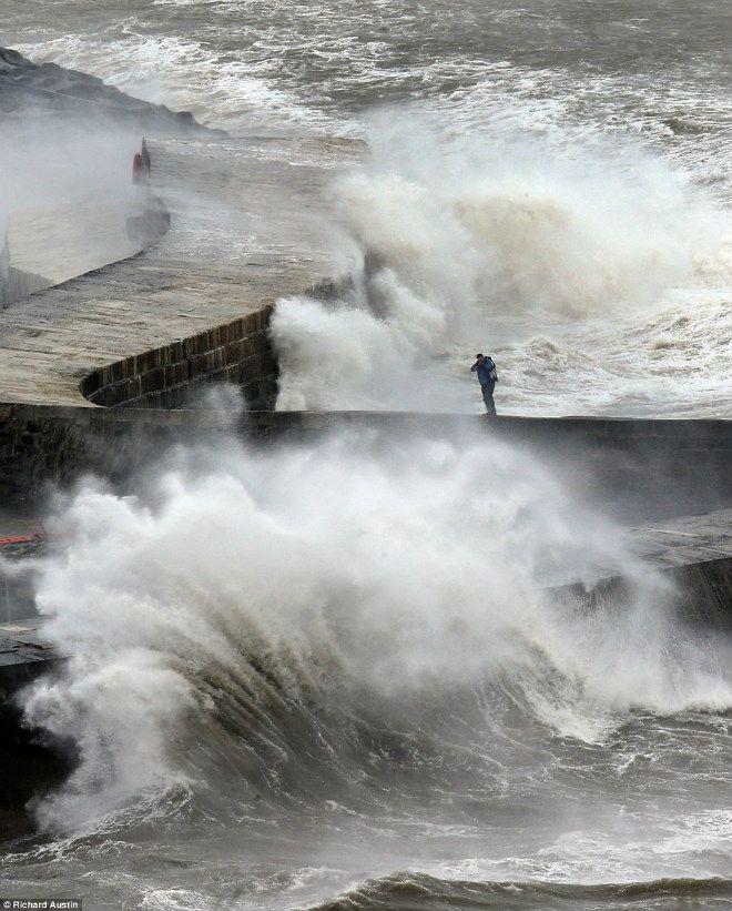 Фотограф ходит между волнами по пирсу в Лайм-Реджис на западе Дорсет, пытаясь сфотографировать буйство стихии. © Ричард Остин