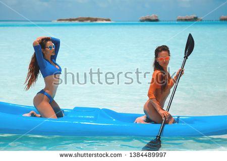 3ec402fef41 Stock Photo: Two sexy bikini models in swimwear posing on kayak, on tropical  beach
