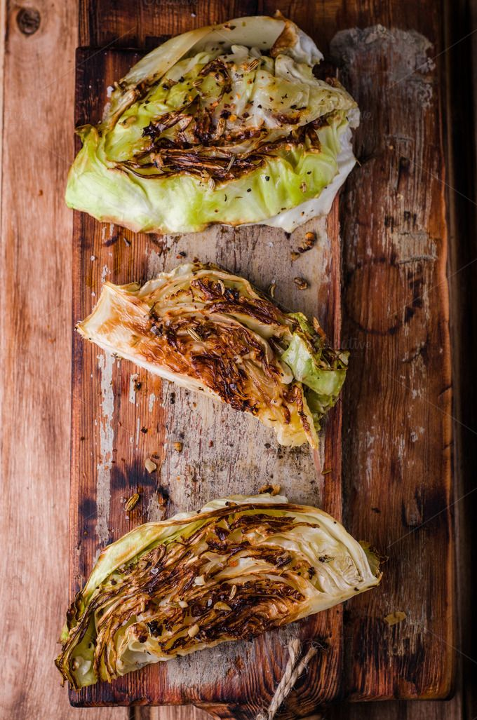 Vegan roasted cabbage steaks on wooden vintage background. Selective focus. Top view by tanchy on @creativemarket