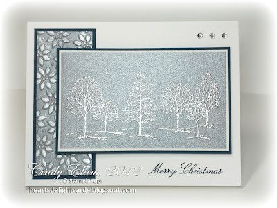 """By Cindy Elam. Focal image: Stamp trees from """"Lovely as a Tree"""" in VersaMark on brushed silver cardstock. Heat emboss with silver powder. Sponge with frost white shimmer paint. Mat on white then navy cardstock. Side panel: Dry emboss brushed silver cardstock in """"Petals-A-Plenty"""" folder (SU); mat on navy. Stamp sentiment in navy. Attach panels. Add gems."""