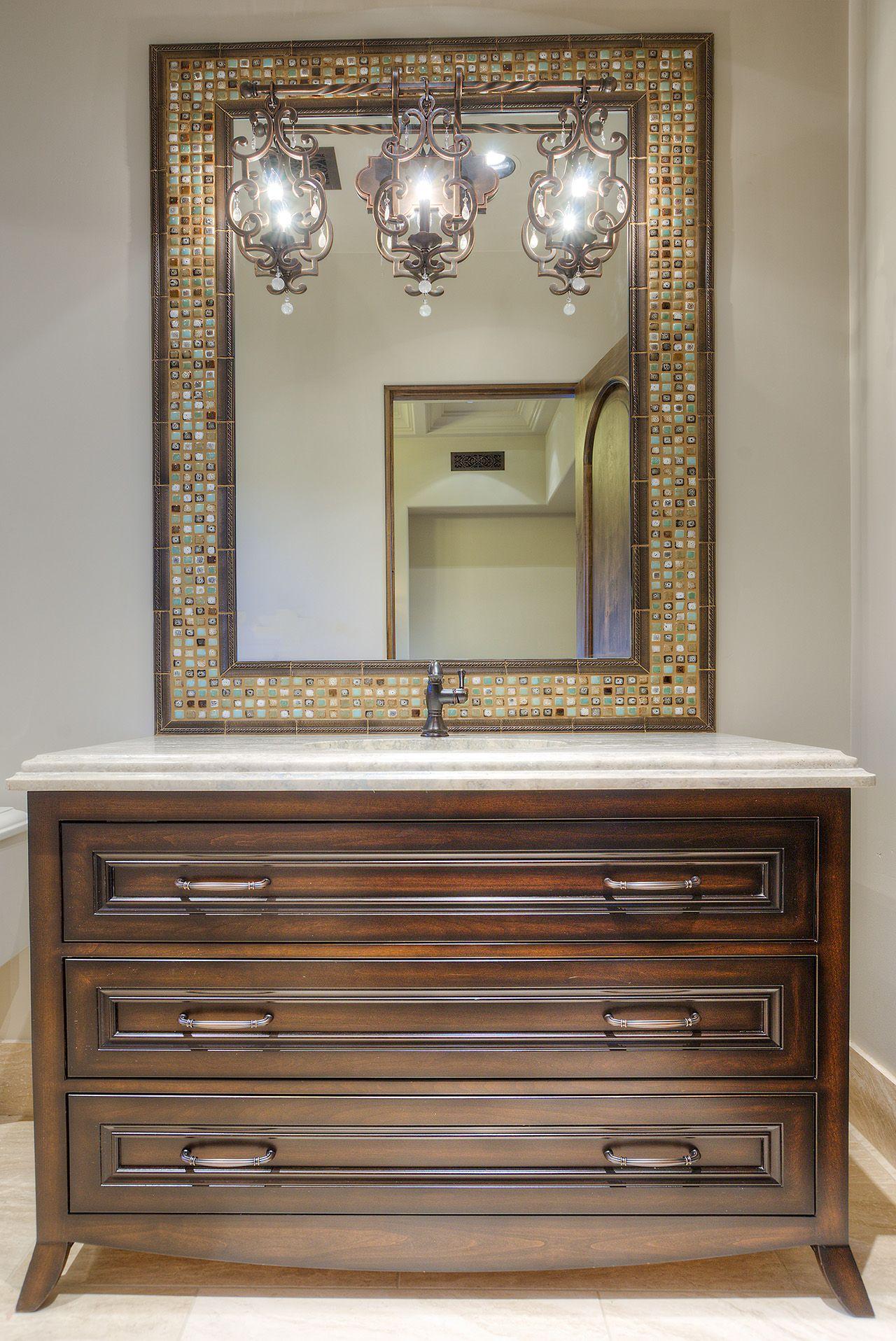 Furniture Style Vanity With A Mosaic Mirror Behind Elegant Vanity Lighting.