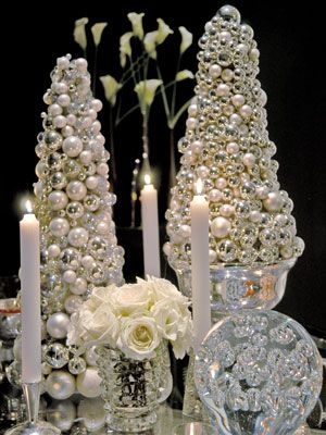 """For a striking addition to any table, create a small silver """"tree."""" Buy an 18-inch-tall Styrofoam cone form, and completely cover it with small Christmas balls in matte and shiny finishes."""