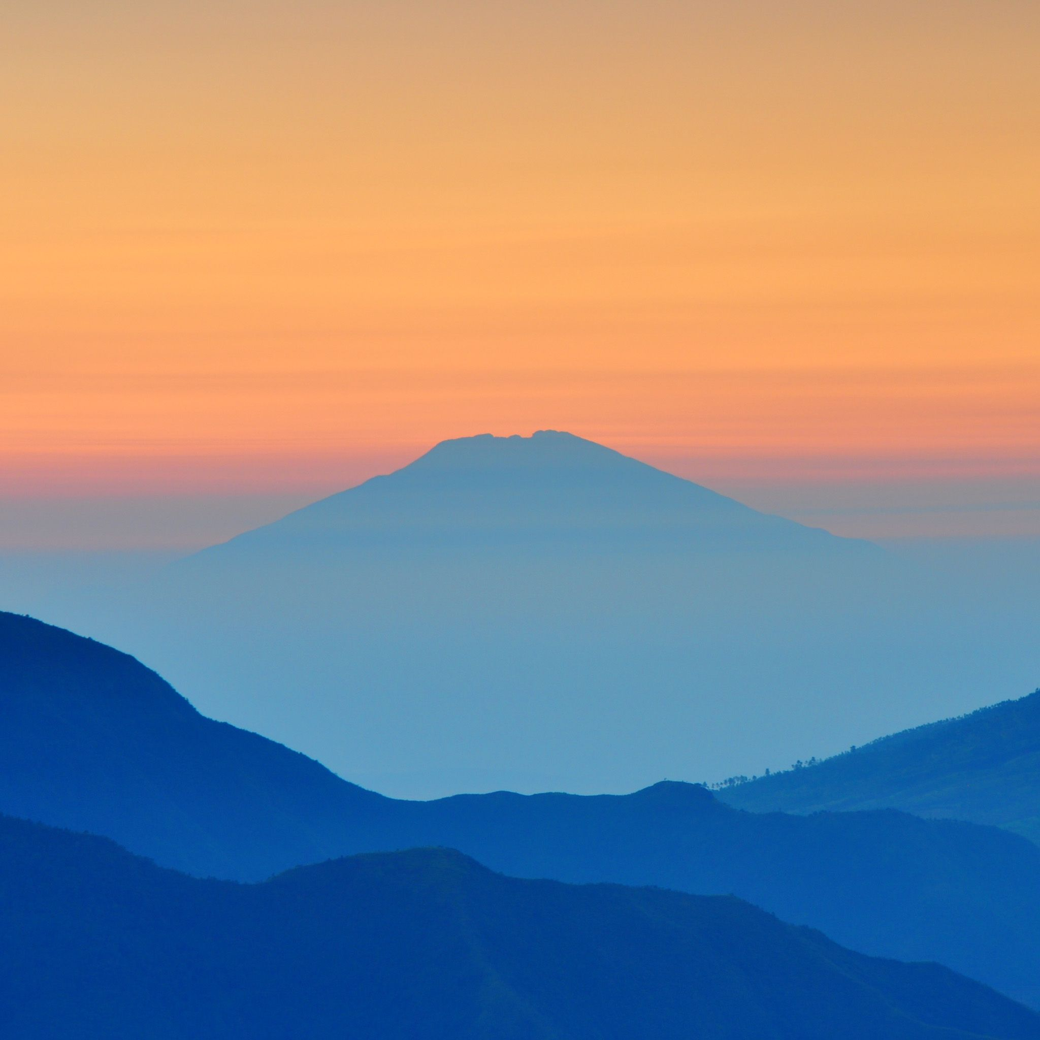 Orange sky and blue mountains landscape. In iPad wallpaper