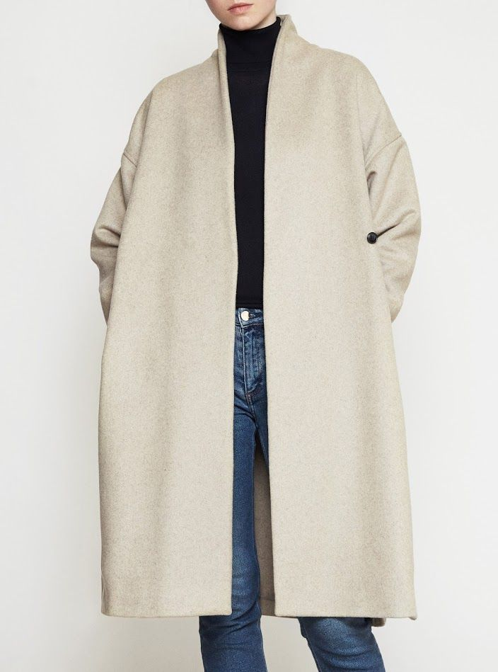 <p>A classic long wrap-around coat from Totême. This  long wool coat is a…