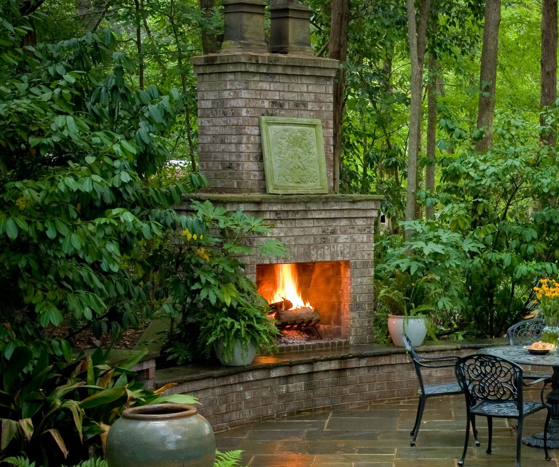 Outdoor brick fireplace in the woods outdoor dining slate patio seating wall outdoor entertaining